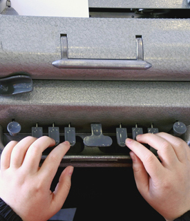 A child learns how to use a Braille typewriter.